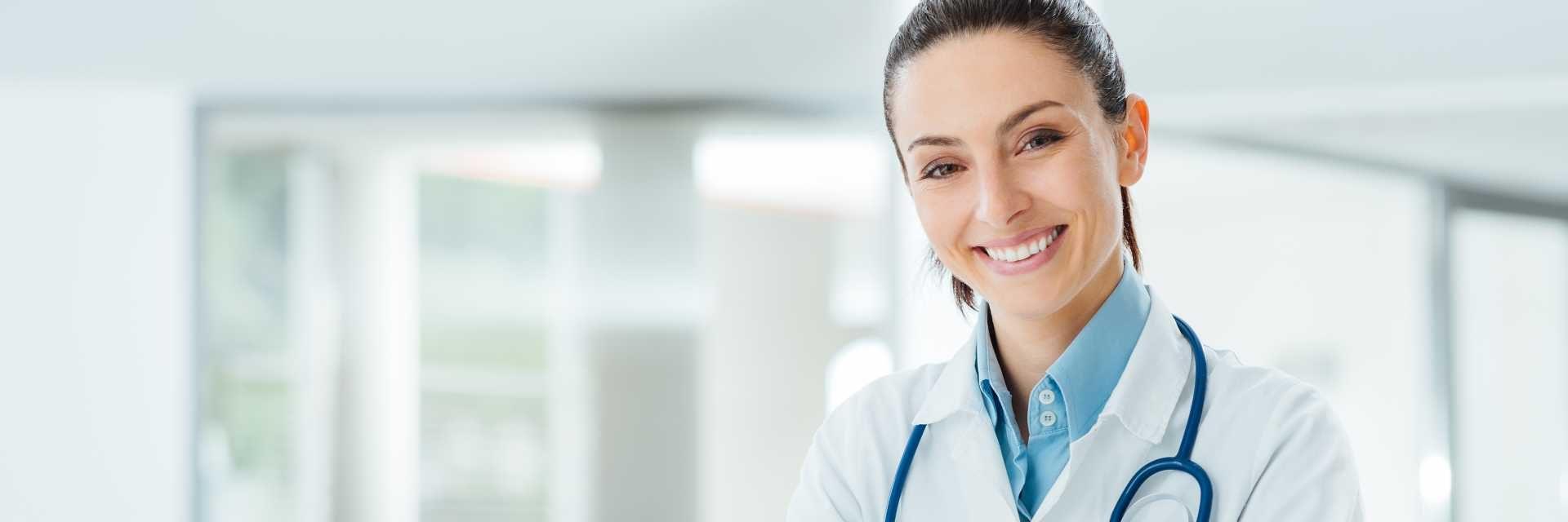 Zuversichtlich Ärztin, die am Schreibtisch sitzt und an Kamera-, Gesundheits- und Präventionskonzept lächelt