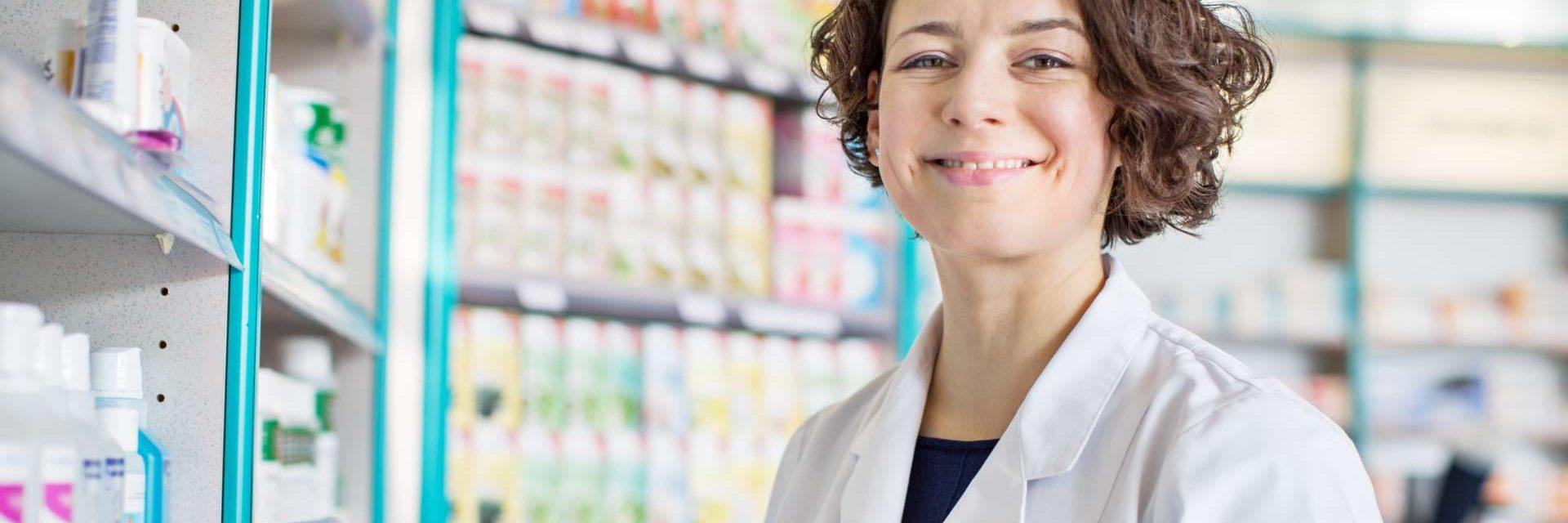 Weibliche Apothekerin mit einer digitalen Tablette in Drogerie, die durch Medizinregale steht