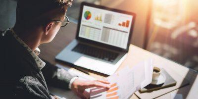Junger Finanzmarktanalyst in Brillen, die am sonnigen Büro auf Laptop arbeiten, während sie am Holztisch sitzen. Geschäftsmann analysieren Dokument in seinen Händen. Graphen und Diagramm auf Notizbuchbildschirm. Unscharf.
