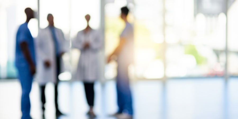 Unscharfe Aufnahme eines Teams von Ärzten, die zusammen in einem Krankenhaus stehen