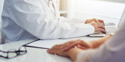 Männlicher Arzt mit Patient, der am Schreibtisch sitzt und auf Laptop schreibt. Beratung im Büro.