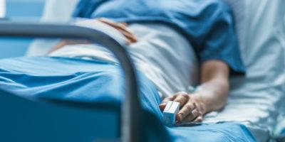 Im Krankenhaus schläft ein kranker männlicher Patient auf dem Bett. Das Gerät zur Herzfrequenzmessung befindet sich an seinem Finger.
