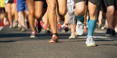 Marathonlaufrennen im Licht des Abends, auf Stadtstraßendetail auf Beinen laufend