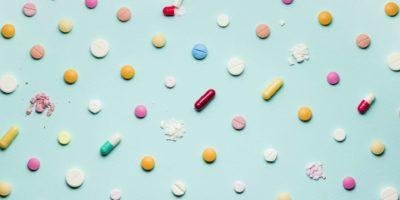 Ein Foto von verschiedenen Arzneimitteln, Tabletten und Pillen auf blauem Hintergrund.