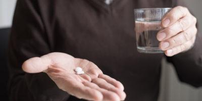Alter Mann, der eine Pille trinkt