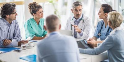 Männlicher Arzt und seine Kolleginnen sprechen mit einem Team von Geschäftsleuten bei einem Treffen im Krankenhaus.