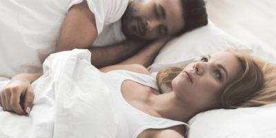 Draufsicht des traurigen Mädchens, das an Schlaflosigkeit leidet. Sie liegt in der Nähe ihres Freundes auf dem Bett und schaut nachdenklich auf