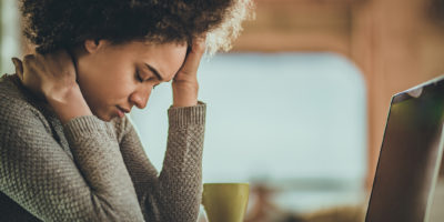 Junge schwarze Frau, die Kopfschmerzen erfährt, nachdem sie zu Hause am Laptop gearbeitet hat.