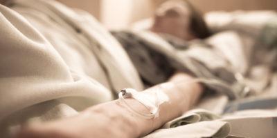 Frau im Krankenhausbett mit iv auf ihrem Arm.