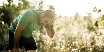 Müder männlicher Jogger, der im Wald biegt. Mittlerer erwachsener Mann ist in Sportkleidung. Er trainiert an einem sonnigen Tag im Wald.