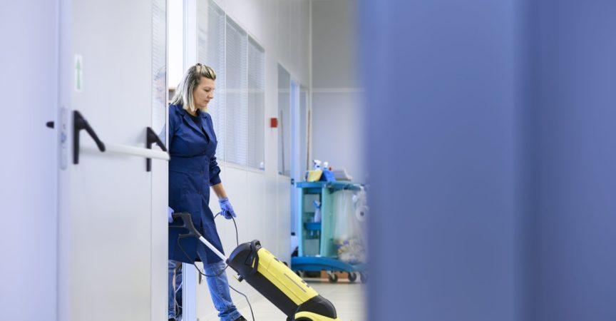 Frauenarbeit, professionelles Dienstmädchen, das Boden mit Maschinen im Industriegebäude reinigt und wäscht. Kopierraum in voller Länge