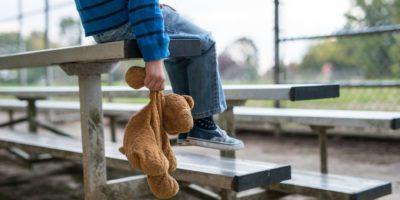 Junge, der allein auf Tribünen sitzt und Teddybär hält.