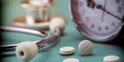 Weißes Pad neben einem Manometer zur Messung des Blutdrucks und eines Stethoskops in einem Krankenhaus, konzeptionelles Bild