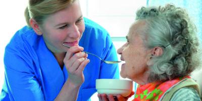 ältere Frau 90 Jahre alt, die von einer Krankenschwester gefüttert wird