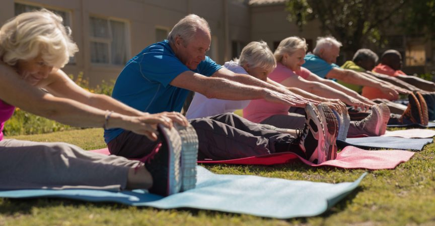 Seitenansicht der Gruppe der aktiven älteren Leute, die ihre Beine auf der Yogamatte im Park trainieren und kratzen