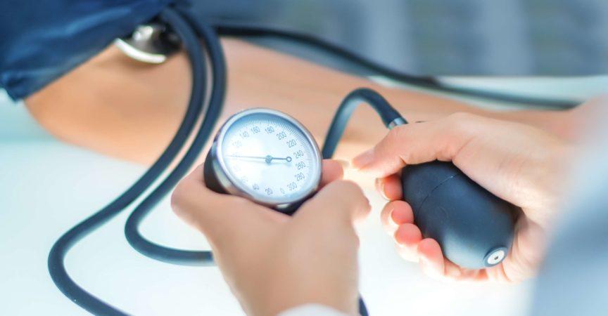 Arzt prüft den Blutdruck mit dem Blutdruckmessgerät im Fokus.