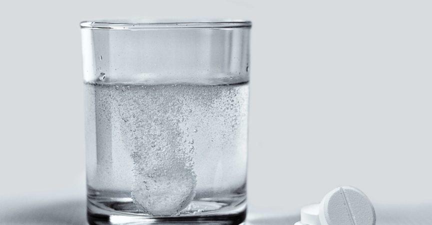 Nahaufnahme von Brausetabletten, die sich in einem Glas Wasser auflösen