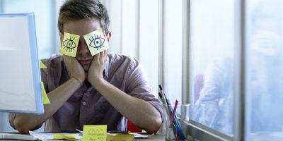 Ein junger Angestellter schläft im Büro und versteckt sich mit Posits in den Augen