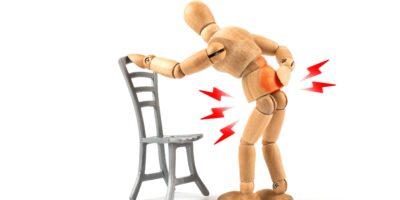 Holzpuppe hat Rückenschmerzen durch falsches Sitzen oder Stehen