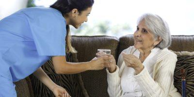 Gesundheitsthemen. Pflegeheimhilfe. Junge hispanische Ärztin, die ältere Frau hilft, eine Pille nimmt