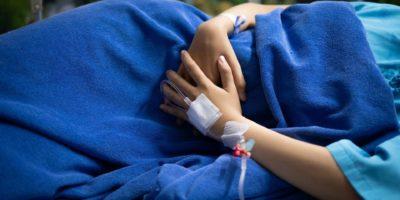 Patientin, die unter Bauchschmerzen leidet, während sie auf Krankenhausbett liegt.