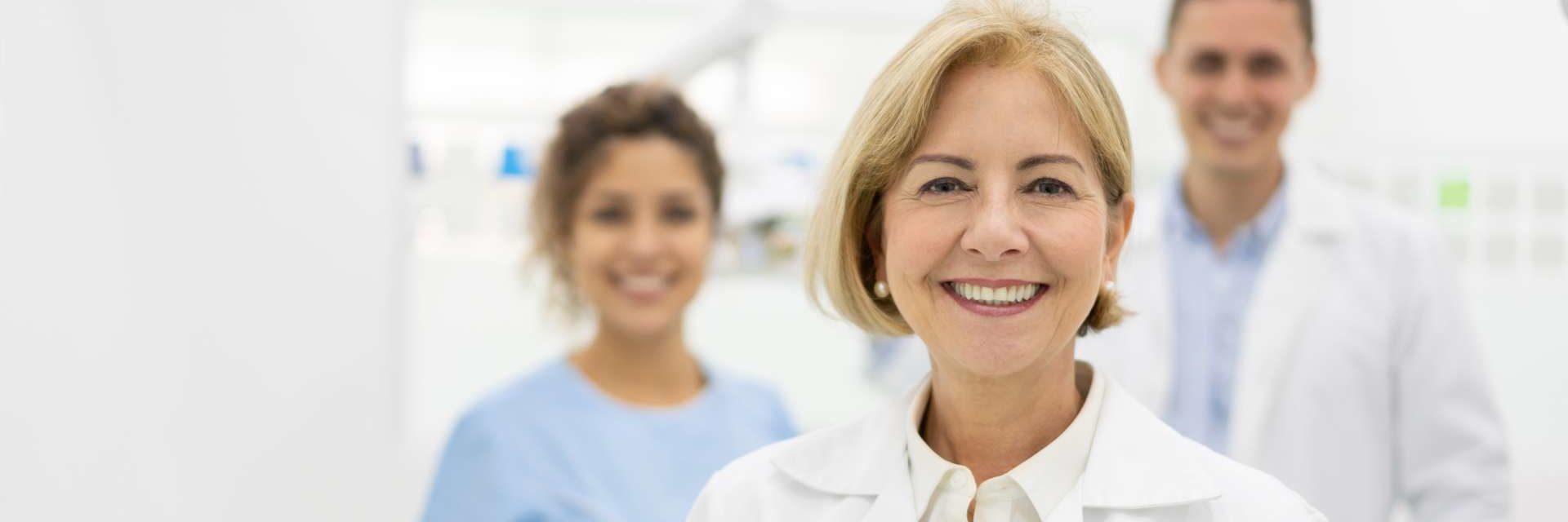 Porträt des glücklichen Zahnarztes im Büro mit ihrem Team und hält einen Tablet-Computer und schaut lächelnd in die Kamera