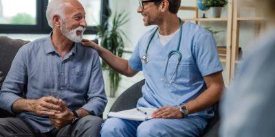 Glücklicher Arzt, der mit älteren männlichen Patienten während eines Hausbesuchs spricht.