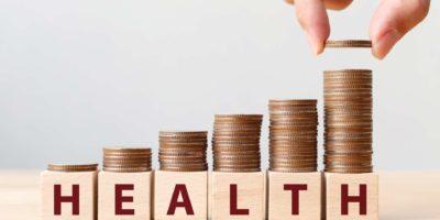 Hand, die Münzen auf Stapeltreppe als Schritt wachsendes Wachstum und Holzwürfelblock mit Wort GESUNDHEIT setzt. Investment Kranken- und Versicherungsfondskonzept