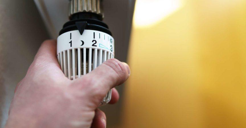 Hand des Mannes, der das Heizkörperthermostatventil auf das Mond- (Nacht-) Symbol einstellt, Symbol zum Sparen von Geld bei Heizkosten oder bei niedriger Temperatureinstellung