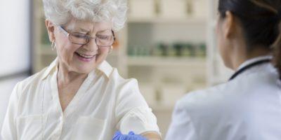 Senior Apothekenkunde bekommt nach Grippeschutzimpfung ein Pflaster
