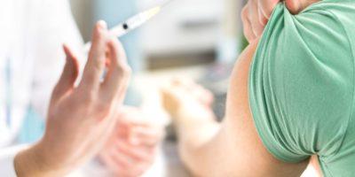Arzt, der dem Patienten Impfstoff, Grippe oder Influenza verabreicht oder eine Blutuntersuchung mit einer Nadel durchführt. Krankenschwester mit Injektion oder Spritze.