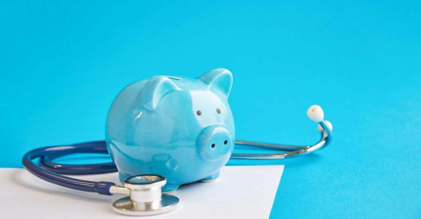 Sparschwein mit Stethoskop lokalisiert auf blauem Hintergrund. Steuervergleichskonzept. Medizinische Kostenabzüge und Steuererleichterungen