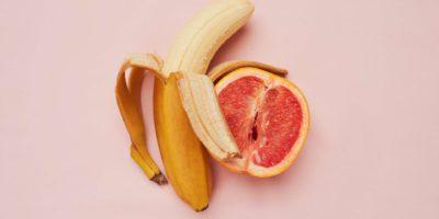 Studioaufnahme einer Banane und einer Grapefruit in einer suggestiven Position vor einem rosa Hintergrund
