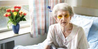 Alte Frau im Spital sitzt im Bett