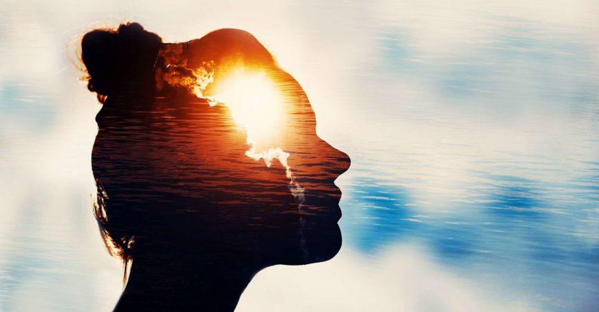 Der Lichtkopf. Schattenbild der jungen Frau auf Himmelhintergrund mit Sonne in ihrem Kopf.