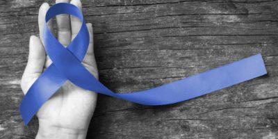 Dunkelblaues Band symbolisch für Dickdarmkrebs und akutes Atemnotsyndrom (ARDS) auf der Hand des Unterstützers (isoliert mit Clipping-Pfad)