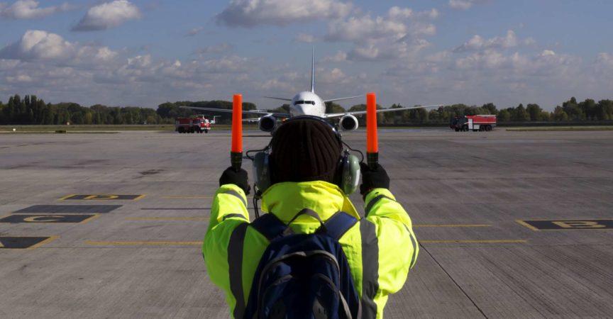 Ein Vorgesetzter hilft beim Flugzeugparken am Flughafen