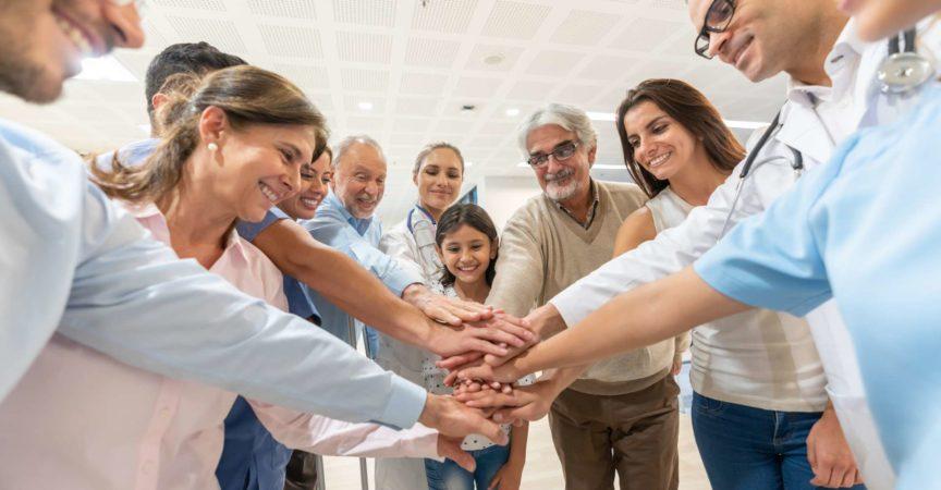 Gruppe von Gesundheitspersonal und Patienten unterschiedlichen Alters in einer Gruppe, alle mit Händen beim Lächeln im Krankenhaus