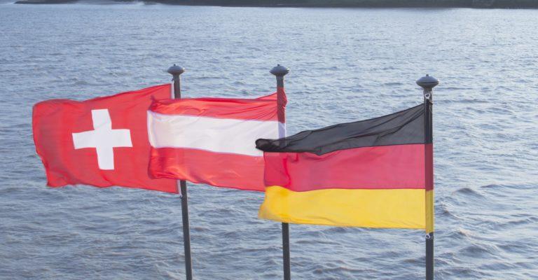 Eine Schweizer, österreichische und deutsche Flagge am Flussufer