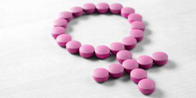 Weibliche Gesundheit. Geschlechtssymbol aus rosaroten Pillen oder Tabletten auf Holztisch
