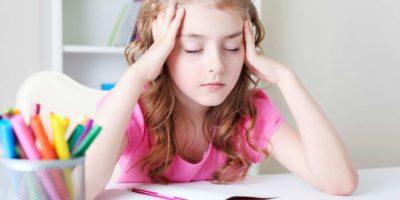 Kindermädchen, das am Schreibtisch Tisch sitzt, lernt Lektionen headacke.Müde von Studienkind