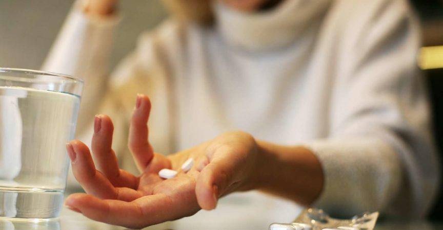 Schließen Sie oben von den Frauenhänden, die eine Pille halten.