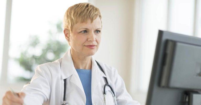 Arzt Arbeiten am Computer am Schreibtisch