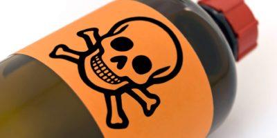 Pharmazeutische Flasche mit Warnsymbol darauf. Weicher Fokus auf den Schädel.