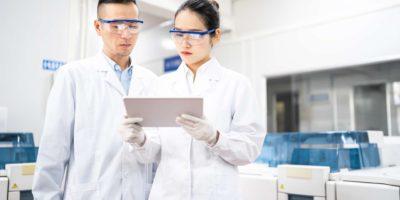 Asiatische Wissenschaftler, die eine digitale Tablette in einem medizinischen Labor verwenden.