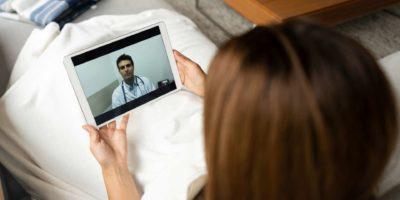 Kranke Frau in Quarantäne im Gespräch mit ihrem Arzt online über einen Tablet-Computer - Gesundheitskonzepte