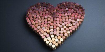 Weinkorken in Herzform auf grauem Hintergrund angeordnet