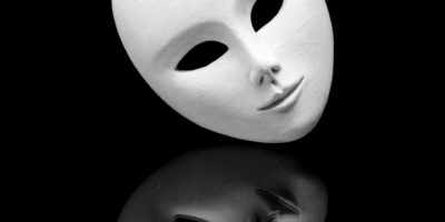 weiße teilnahmslose venezianische Maske und ihre Reflexion im schwarzen Spiegel