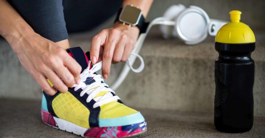 Weibliche Hände, die Schnürsenkel binden. Die Smartwatch befindet sich am linken Handgelenk und die Sportflasche befindet sich neben dem Sportschuh.