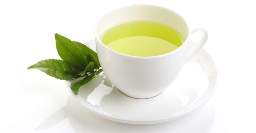 Japanischer grüner Tee und frische grüne Teeblätter auf weißem Hintergrund